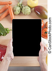 hand with tablet fruits and vegetables
