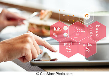 hand with tablet pc and nutritional value chart - food, ...