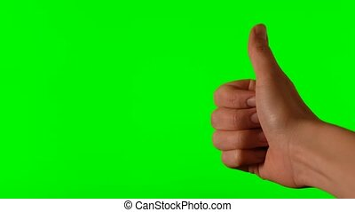 Woman hand with thumb up on a green background close-up