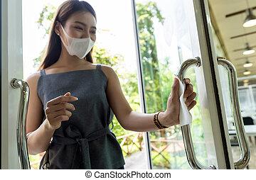 Hand with tissue paper to push restaurant door open.