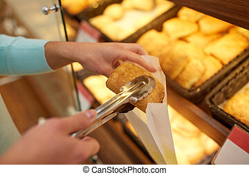 hand with tongs taking bun at bakery or grocery
