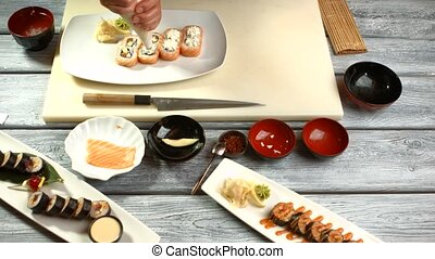 Hand with tool prepares sushi. Small sushi rolls on plate....