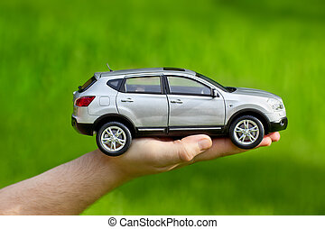 Hand with toy car on grass background.