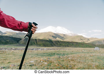 Female hand with trekking pole on background of mountain Elbrus.