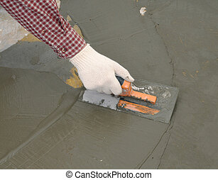 Hand with trowel spreading wet concrete - Construction...