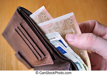 Hand withdrawing money from wallet