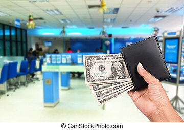 Hand women hold money in black wallet on the bank background