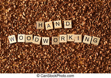 Hand woodworking word writen with letters on a wood chips