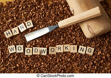 Hand woodworking word writen with letters on wood chips with chisel and mallet