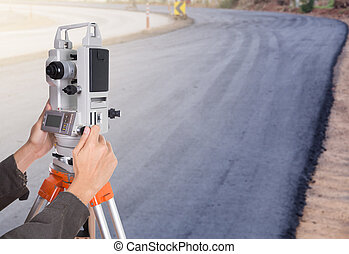 hand working with survey equipment theodolite on a tripod. with road under construction