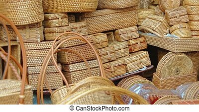 Many, beautiful baskets, hand woven by Balinese artisans, stacked on display for sale at a local, public market. 4k footage