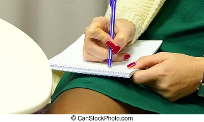 hand writes to a notebook lying on his knee