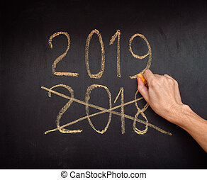 Hand writing 2019 and crossing out 2018 on a blackboard. ...