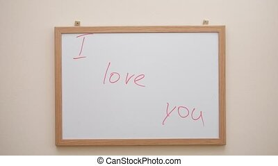 Hand writing and erasing the inscription I love you with red marker on white board