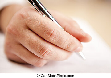 close up of a hand holding a pen