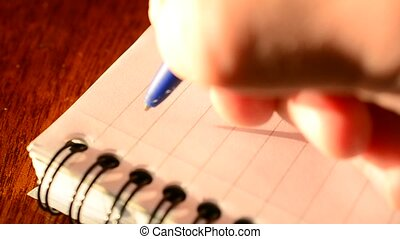Hand writing DEAR DAD with a blue ballpoint pen in notepad....