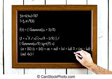 Hand writing formula on chalkboard