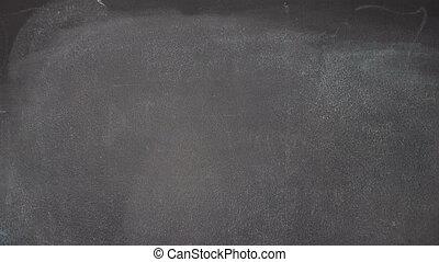 """Hand writing """"FUN"""" on black chalkboard"""
