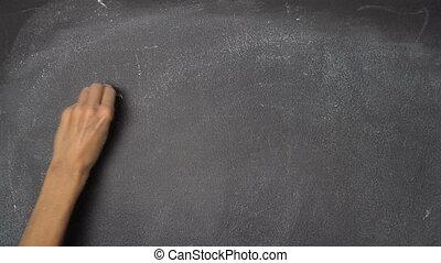 """Hand writing """"GOAL"""" on black chalkboard"""