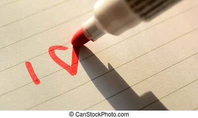 Hand writing I LOVE YOU U with red marker on lined paper...