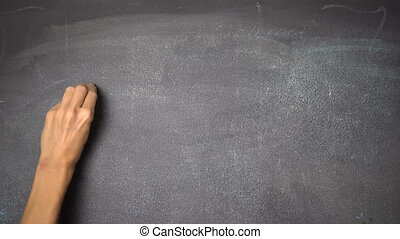 "Hand writing ""SCHOOL"" on black chalkboard - Woman's hand..."