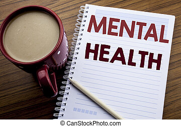 Hand writing text caption inspiration showing Mental Health. Business concept for Anxiety Illness Disorder written on note paper notepad book on the wooden background with coffee and pen.
