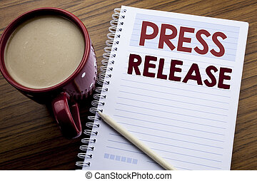 Hand writing text caption inspiration showing Press Release. Business concept for Statement Announcement Message written on note paper notepad book on the wooden background with coffee and pen.