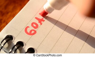 Hand writing the word GOALS with red marker in notepad