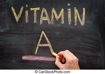 Hand writing Vitamin A on chalkboard. Close up.