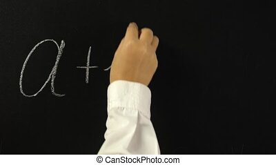 Hand writing with chalk on chalkboard mathematical equation, a plus b equals c