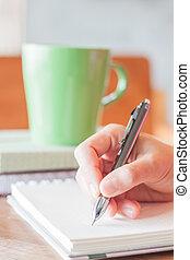 Hand writing with green mug background