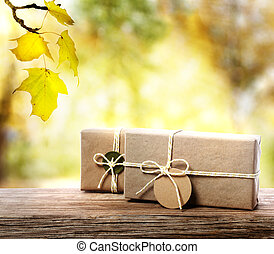 Handcrafted gift boxes on aged wooden boards with an autumn foliage background