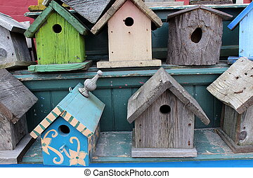 Colorful simple wood birdhouses handcrafted and displayed on shelves for sale at farmer's market.