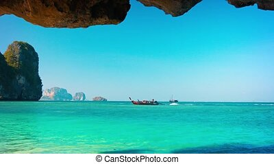 Handcrafted, Wooden Boat Passing a Cave on the Tropical Sea...