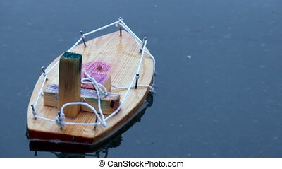Handcrafted wooden boat toy floating water surface...