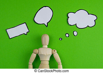 Handcrafted wooden man figure mannequin model dummy doll with blank speech bubble on green background, objects, nobody