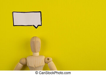 Handcrafted wooden man figure mannequin model dummy doll with blank speech bubble on orange background, objects, nobody