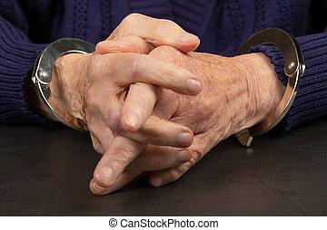 Handcuffed elderly woman