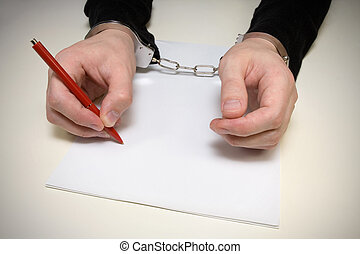 handcuffed man writing a confession of the crime