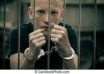 Handcuffed teenage boy behind bars in a prison cell staring...