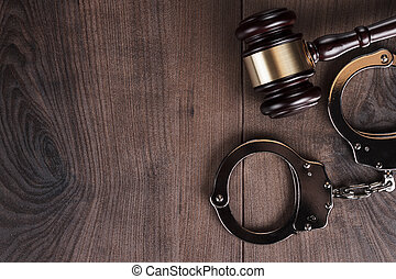 handcuffs and judge gavel on wooden background - handcuffs...