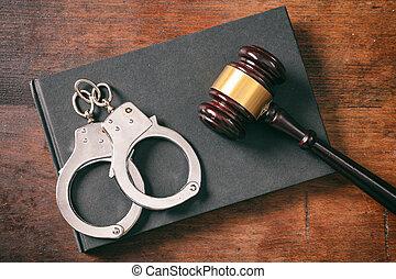 handcuffs, gavel, op, boek, op, een, houten, achtergrond.