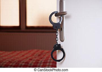 handcuffs on bedroom door handle