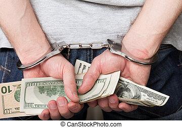 Handcuffs on hands holding money - Handcuffs arrests dollar...