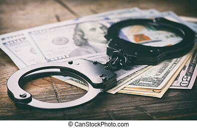 Handcuffs on money. Criminal concept