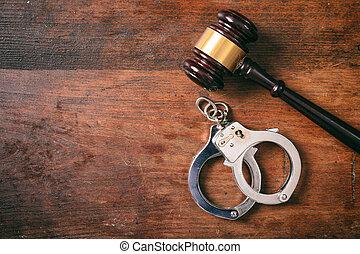handcuffs, vrijstaand, en, een, gavel, met, de ruimte van het exemplaar, op, een, houten, achtergrond.