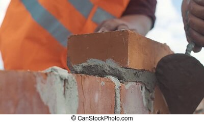 Handed shot of Bricklayer builds wall.