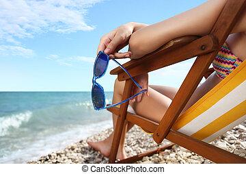handen, met, zonnebrillen, op het strand