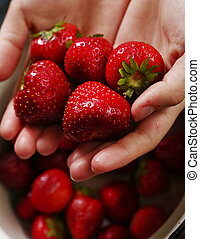 handful of garden strawberries on green background