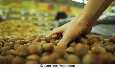 Handful of hazelnuts in a supermarket, slow motion video -...